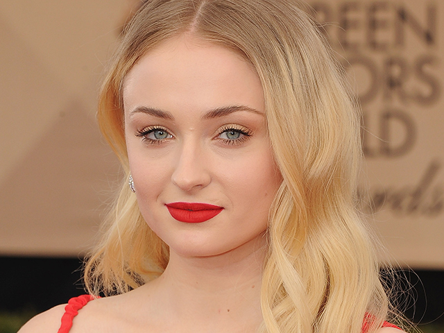 Sophie Turner turned the heat up a notch on the red carpet with a bright, matte lip colour of the same shade as her gown.